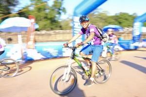 Narla riding his bike through the finish line in Cambodia.