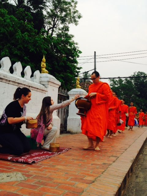 Naida (left) and Kena (right) from the Journeys Within Team giving morning alms to the monks of Luang Prabang.