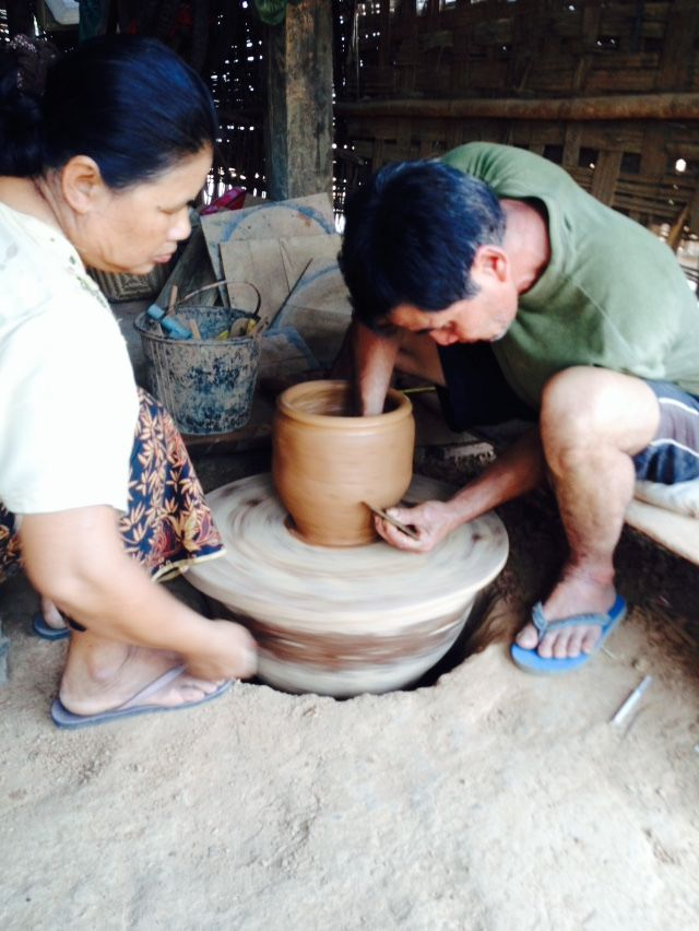 A man and his wife work as a team to create a new clay pot.